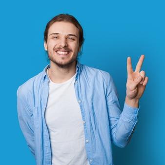 Toothily glimlachende man met baard en lang haar die vrede en vriendschap gebaren op een blauwe studiomuur
