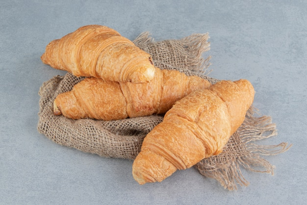 Toothsome croissant op handdoek, op de marmeren achtergrond. hoge kwaliteit foto
