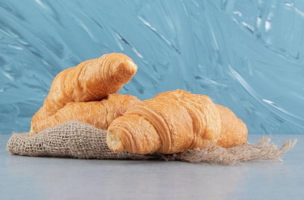 Toothsome croissants op handdoek, op de blauwe achtergrond. hoge kwaliteit foto