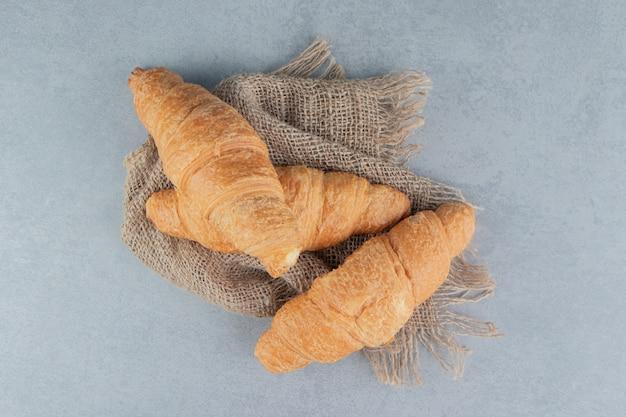 Toothsome croissants op handdoek, op de marmeren achtergrond. hoge kwaliteit foto