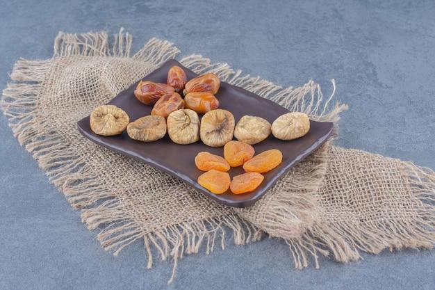 Toothsome gedroogde vruchten op het bord, op de onderzetter, op de marmeren achtergrond.