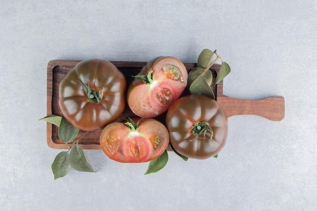 Toothsome tomaat op het bord, op het marmeren oppervlak