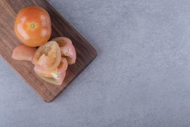 Toothsome tomaten op snijplank, op de marmeren achtergrond.