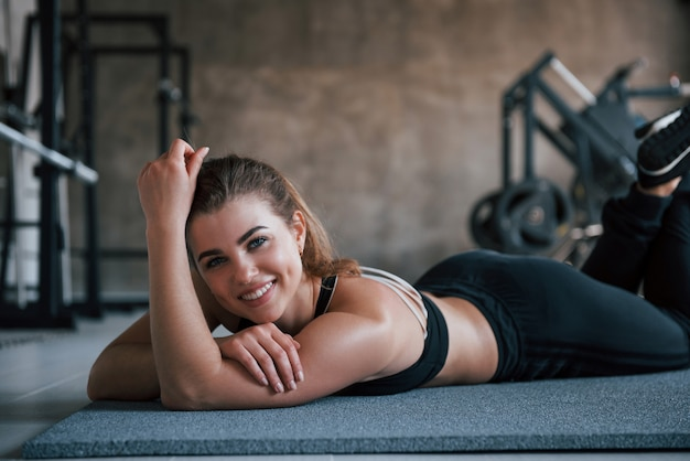 Toothy glimlach. foto van prachtige blonde vrouw in de sportschool tijdens haar weekend