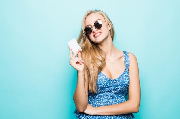 Toothy glimlachende jonge vrouw in zonnebril houdt creditcard op blauwe achtergrond.
