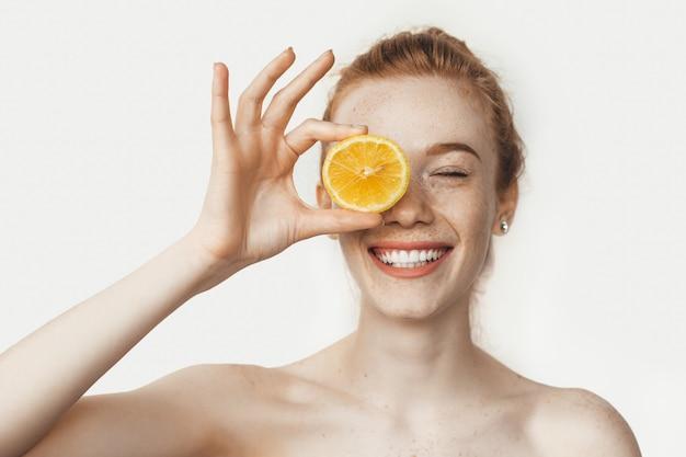 Toothy glimlachende vrouw met blote schouders en sproeten voor haar oog met een citroen die zich voordeed op een witte muur