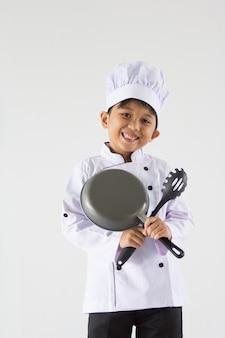 Toothy jongen in chef-kok eenvormig op geïsoleerd wit