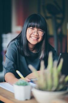 Toothy lachend gezicht van aziatische tiener die aan computer thuis werkt