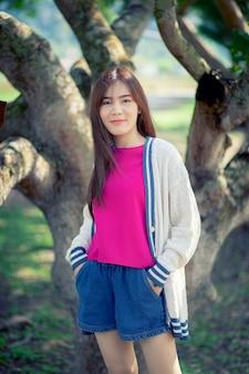 Toothy lachend gezicht van mooie aziatische jongere vrouw die zich in park bevindt