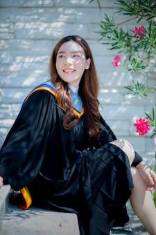 Toothy lachend gezicht van mooie aziatische jongere vrouw dragen van universiteit afgestudeerd kleding geluk emotie