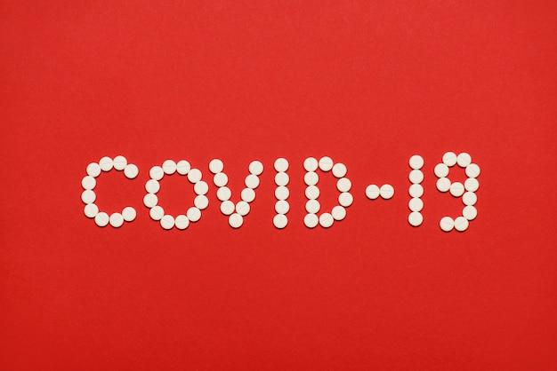 Top boven overhead close-up foto van de inscriptie van coronavirus covid-19 gemaakt van witte ronde pillen geïsoleerd op heldere rode achtergrond