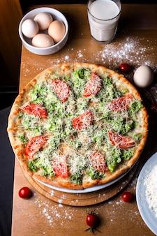 Top caesar pizza met tomaten en parmezaanse kaas op houten tafel
