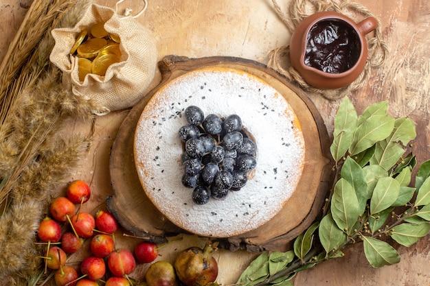 Top close-up bekijken een cake een cake op het bord snoepjes chocolade bessen tarwe oren