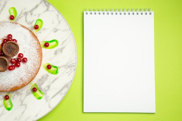 Top close-up bekijken een cake notebook een cake met wafels bessen
