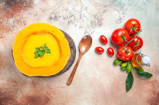 Top close-up bekijken een soep pompoensoep op het bord olie citrusvruchten tomaten lepel
