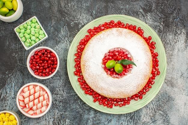 Top close-up cake een smakelijke cake kommen van citrusvruchten verschillende snoepjes