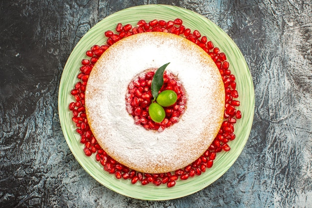 Top close-up cake met bessen de cake met granaatappel citrusvruchten op de witte plaat