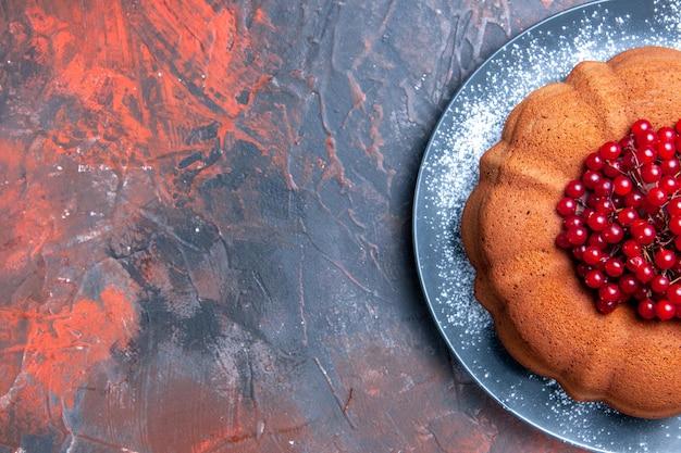 Top close-up cake met rode aalbessen de smakelijke cake met rode aalbessen op de blauwe tafel