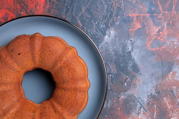 Top close-up cake op de blauwe achtergrond blauwe ronde plaat van een smakelijke cake