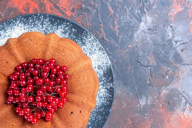Top close-up cake smakelijke cake met rode aalbessen op de rood-blauwe tafel
