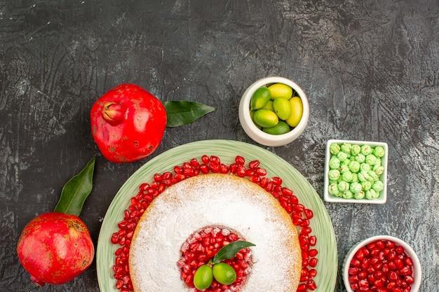 Top close-up cake snoep granaatappels een smakelijke cake citrusvruchten groene snoepjes