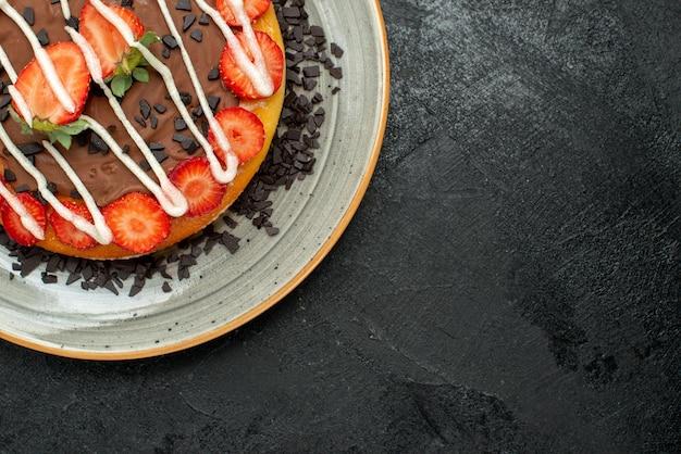 Top close-up dessert smakelijke cake met stukjes chocolade en aardbeien op een witte plaat aan de linkerkant van de donkere tafel
