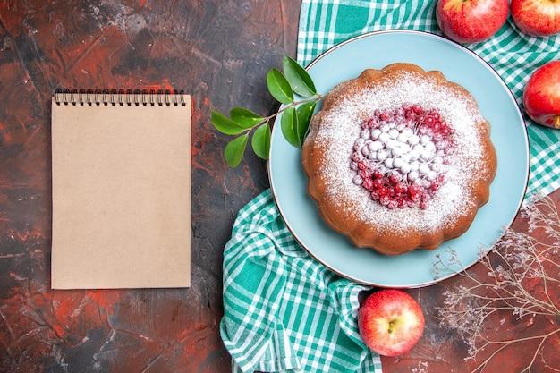 Top close-up een cake een cake met rode aalbessen appels op het geruite tafelkleed crème notebook