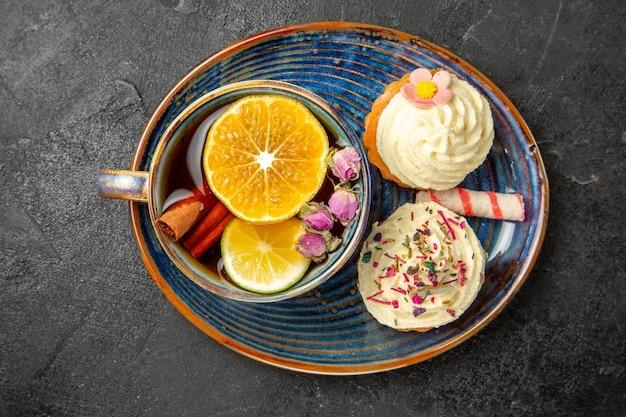 Top close-up een kopje thee met citroen twee smakelijke cupcakes met witte room snoep en een kopje met kruiden en citroen op de blauwe schotel op de zwarte tafel