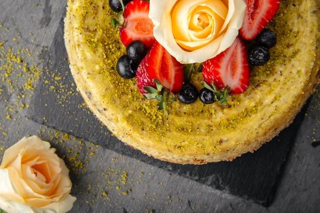 Top close-up op pistache cheesecake gegarneerd met bessen en roos