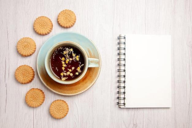 Top close-up thee met koekjes witte kop kruidenthee naast het witte notitieboekje en koekjes op de witte tafel