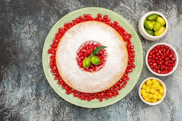 Top close-up uitzicht cake en snoep een bord cake met granaatappel kommen van citrusvruchten snoepjes