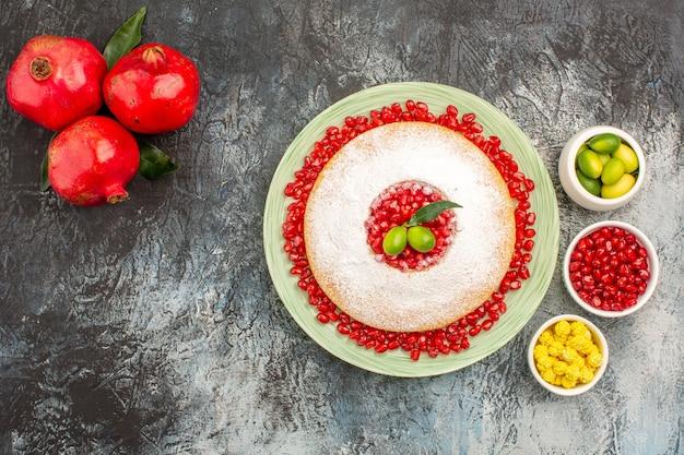 Top close-up uitzicht cake en snoep een taart kommen van citrusvruchten snoepjes drie rode granaatappels