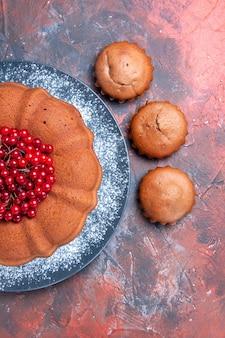 Top close-up uitzicht cake met bessen cake met rode aalbessen op de plaat drie cupcakes