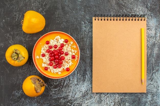 Top close-up weergave bessen dadelpruimen de smakelijke bessen in de oranje kom notebook potlood