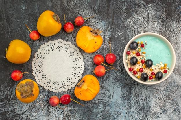 Top close-up weergave bessen kersen dadelpruimen rond kant kleedje naast de kom met bessen