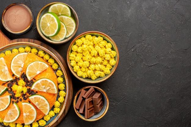 Top close-up weergave cake en snoep in kom smakelijke oranje cake en kommen gele snoepjes chocolade schijfjes limoen en chocolade crème op de zwarte tafel