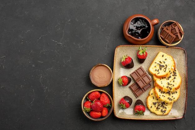 Top close-up weergave cake met aardbeien chocolade en aardbei in bruine kommen en plaat van cake met chocolade bedekte aardbeien aan de rechterkant van de tafel