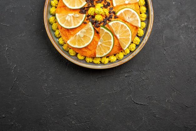 Top close-up weergave cake smakelijke cake met plakjes citrusvruchten op de donkerpaarse achtergrond