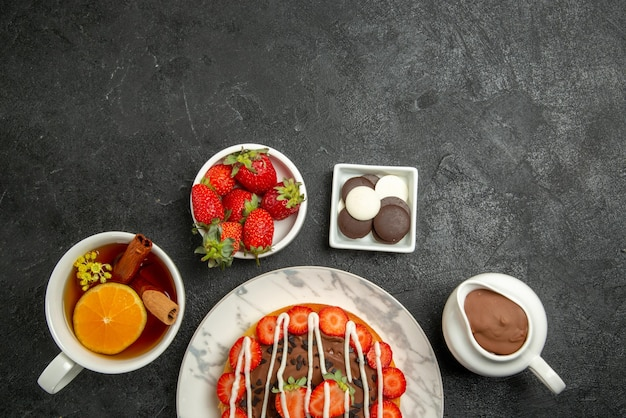 Top close-up weergave chocolade crème aardbeien smakelijke cake en een kopje thee met citroen en kaneel naast de kommen chocolade aardbeien en chocolade crème op de donkere tafel
