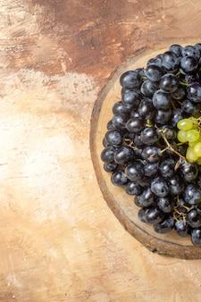 Top close-up weergave druiven groene en zwarte druiven op het bord van de keuken