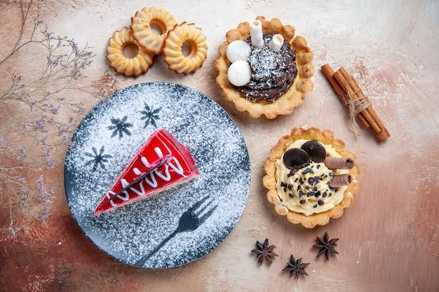 Top close-up weergave een cake cupcakes koekjes een cake kaneelstokjes steranijs boomtakken