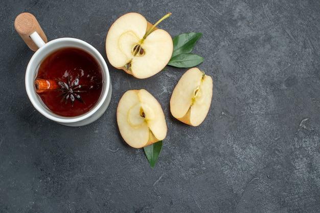 Top close-up weergave een kopje thee een kopje thee met kaneelstokjes naast de appelschijfjes