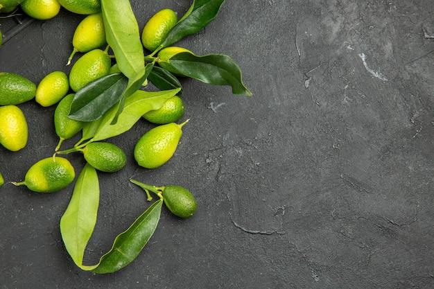 Top close-up weergave fruit citrusvruchten met bladeren op de donkere tafel