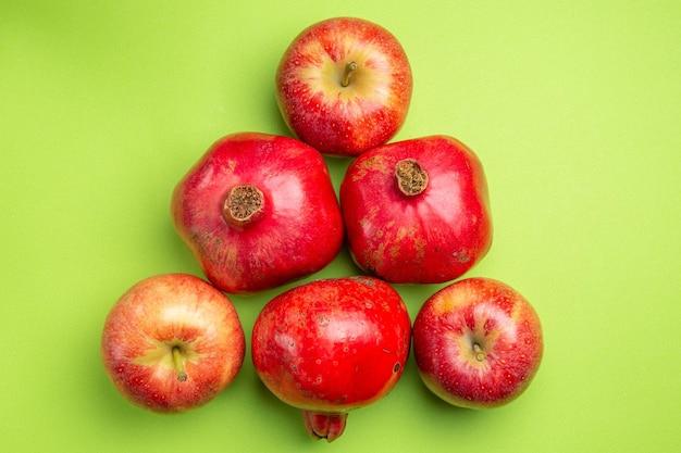 Top close-up weergave fruit de smakelijke granaatappels en drie rode appels op het groene oppervlak