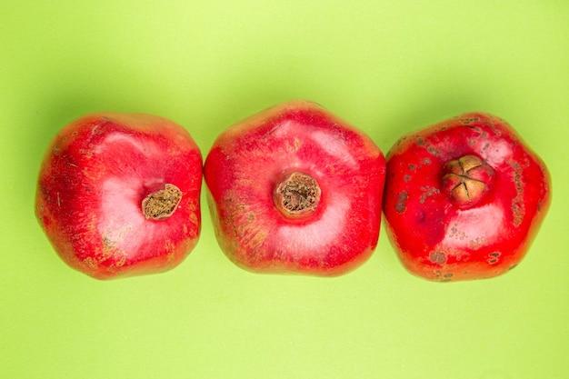 Top close-up weergave fruit drie rijpe smakelijke granaatappels op de groene tafel