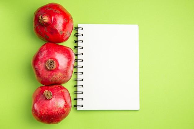 Top close-up weergave fruit drie smakelijke granaatappels wit notitieboekje op de groene tafel