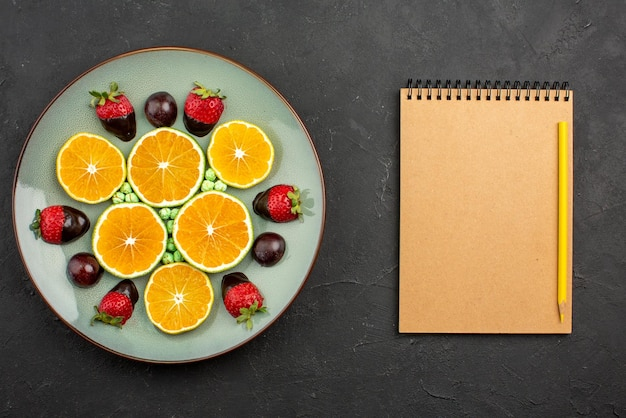 Top close-up weergave fruit en chocolade gehakte sinaasappel met chocolade bedekte aardbeien en groene snoepjes naast crème notitieboekje en geel potlood op donkere tafel