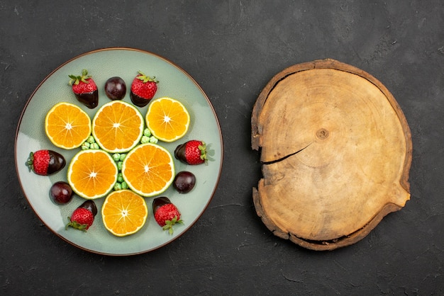 Top close-up weergave fruit en chocolade gehakte sinaasappel met chocolade bedekte aardbeien en groene snoepjes naast snijplank op donkere ondergrond