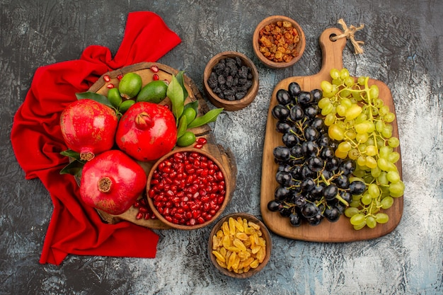 Top close-up weergave fruit gedroogde vruchten druiven op het bord granaatappels op het rode tafelkleed
