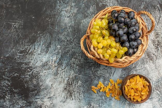 Top close-up weergave fruit gedroogde vruchten in de kom de smakelijke groene en zwarte druiven
